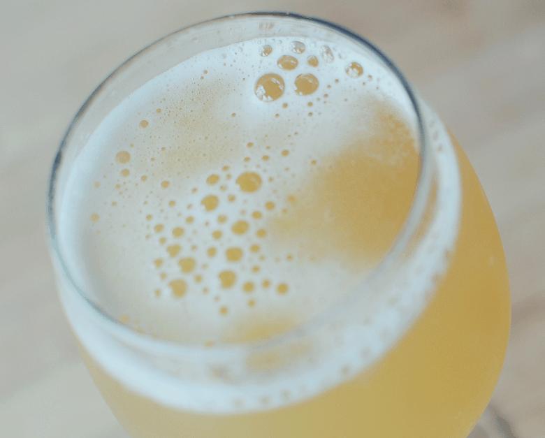 A wine glass full of sparkling kombucha