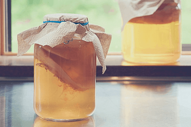 a jar of kombucha with a SCOBY in it