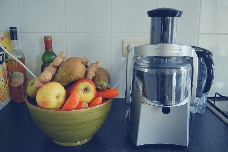 Bowl of fruit next to a juicer