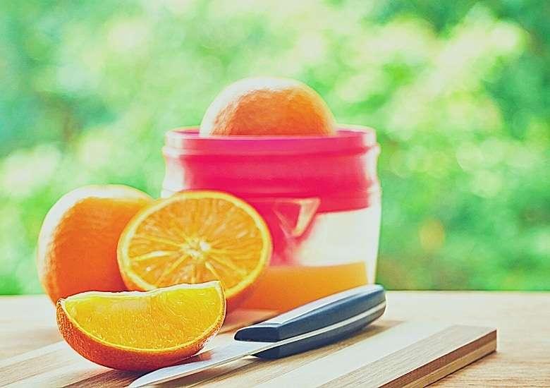 oranges next to an orange juicer