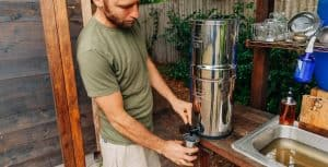 man pouring a glass of Berkey filtered water